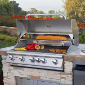 outdoor grill in an outdoor kitchen island with food grilling